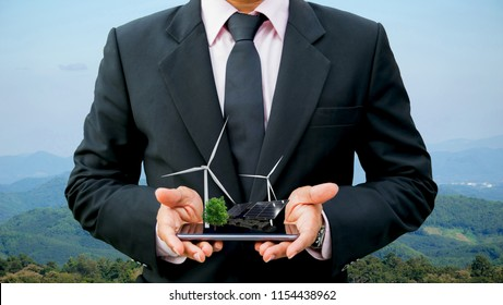 Ecology concept hands holding businessman on a smartphone tree electrical energy clean wind turbine and solar cell the future