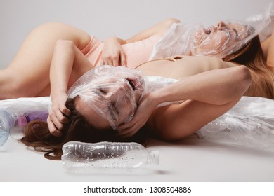 Ecology concept. Natural beauty in plastic world. Two beautiful women lying among empty plastic bottles