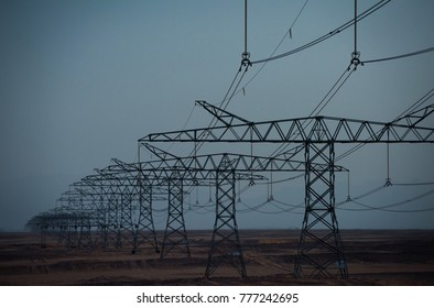 Ecology, eco power, technology concept. Electric energy transmission. Electricity distribution stations. Power line towers in desert on blue sky background. Global warming, climate change.