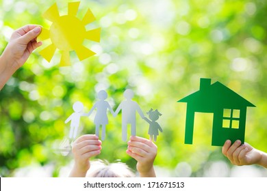 Ecology house and family in hands against spring green background
