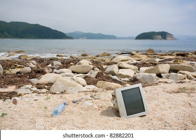 Ecology. Old computer monitor lying discarded on the shore of the sea.