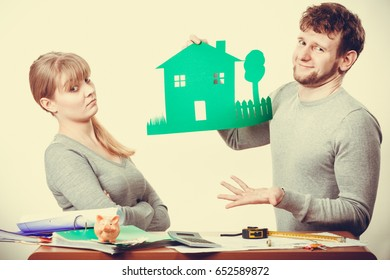 Ecology in practical domestic life. People real estate and house concept. Young dissatisfied couple with green ecological paper house thinking of future.