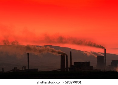 Ecology - the smoking factory chimneys against the setting sun lit up