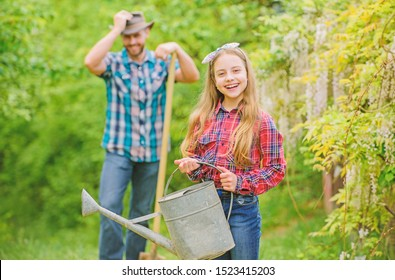 ecology. Watering can and shovel. spring village country. family farm. little girl and happy man dad. earth day. father and daughter on ranch. Working with pleasure. Flowers presentation.