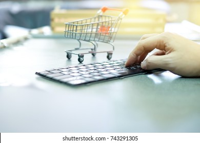 e-commerce business, finger on computer keyboard to order something with 4 wheels mini handcart shopping.