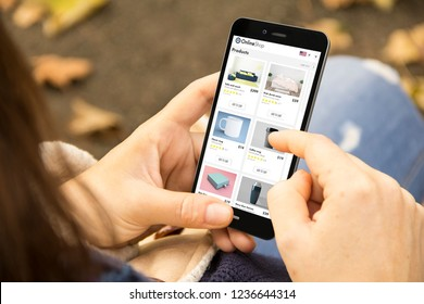 e-commerce concept: woman holding a 3d generated smartphone with online shop on the screen. Graphics on screen are made up.