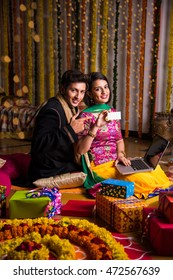 E-commerce and Diwali festival concept - indian young couple purchasing online showing blank discount voucher/card