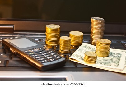 E-commerce. Mobile phone, bills and coins on laptop keyboard