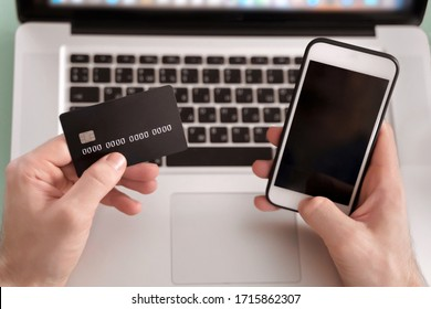 E-commerce and online paying concept. Young businessman using mobile phone and laptop for e-banking. Online trading on the currency exchange. Online payments on website through the phone