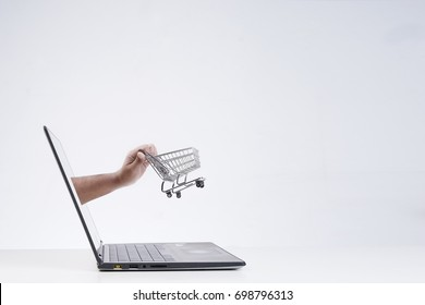 E-commerce or online shopping concept. Shopping cart  pushed out of a laptop.