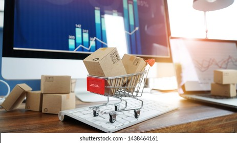 E-commerce. Paper boxes in shopping cart on keyboard and sales data economic growth graph on computer  screen, online shopping and payments, banking, buying and selling services online on network.