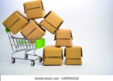 E-Commerce Text in small boxes and shopping cart. Concepts about online shopping. Isolated on white background