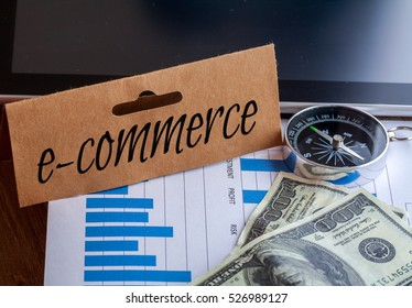 e-commerce Words on tag with dollar note,smartphone,compass and graph on wood backgroud,Finance Concept