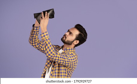 Economic crisis concept. Upset Indian guy with empty wallet on violet background, panorama