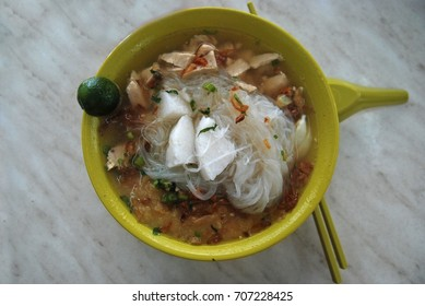 Economic serving of rice vermil in soup with slices of chicken meat garnished with coriander leaves and fried shallots is a favorite breakfast dish in Malaysian locally known as 'Soto'.