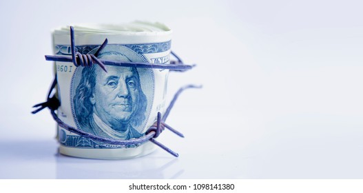 Economic warfare, sanctions and embargo busting concept. US Dollar money wrapped in barbed wire.