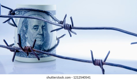 Economic warfare, sanctions and embargo busting concept. US Dollar money  in barbed wire.