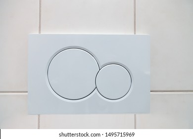 Economic white dual buttons of flush toilet bowl on tiled wall in bathroom. Flushing system in closet