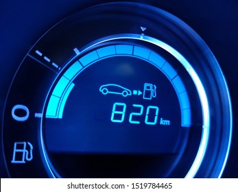 Economical driving. Fuel economy gauge with indication of 820 kilometers remaining to refueling. Close-up of car dashboard fragment.