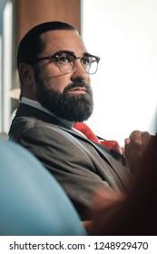 Economist in glasses. Dark-haired bearded economist wearing glasses sitting on sofa in his hotel room