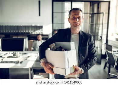 Economist leaving office. Handsome economist leaving the office taking his box with different things