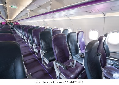 An economy class clean cabin of the airplane - empty purple chairs