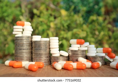 Economy and healthcare concept, orange capsules and white pills on rolls step of coin money, medicines on wood table in blur natural tree