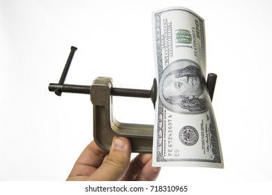 Economy problem.One hundred dollar bill pressured in a  vice isolated on white background. Vice grip squeezing a dollars isolated on white background. Economy under stress