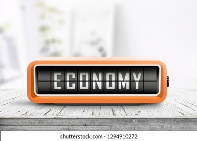 Economy word on an analog device in a bright home on a wooden desk