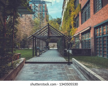 Eco-style in the center of Tbilisi. Modern courtyard in Stamba hotel with beautiful views, alley with a wooden structure. Trees on the background of a brick building.