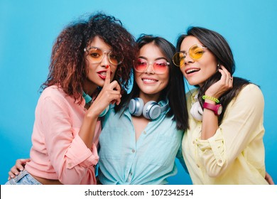 Ecstatic asian girl in blue cotton shirt embracing friends during photoshoot. Indoor portrait of catching african lady with curly hair having fun with female colleagues.