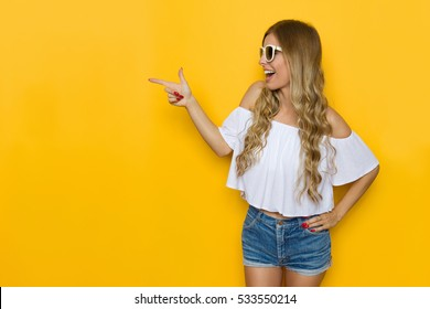 Ecstatic blond young woman in jeans shorts, white shirt and sunglasses holding hand on hip, looking away and pointing, Three quarter length studio shot on yellow background.