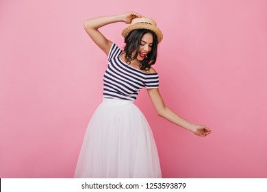 Ecstatic brunette girl in straw hat dancing on pink background. Studio shot of slim fascinating woman having fun.