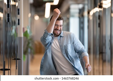 Ecstatic excited male winner dancing in office hallway laughing celebrating work achievement professional win, happy overjoyed business man enjoy victory dance euphoric about success reward promotion
