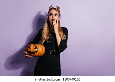 Ecstatic female vampire thinking about something evil. Studio portrait of witch in black dress holding pumpkin.