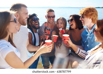 Ecstatic friends cheering up with drinks on the beach