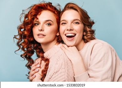 Ecstatic friends embracing on blue background. Studio shot of cheerful girls looking at camera.
