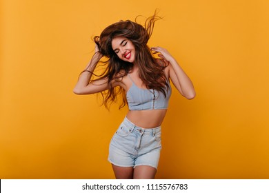 Ecstatic girl with inspired face expression dancing on yellow background. Studio shot of glamorous tanned female model in trendy shorts enjoying photoshoot.
