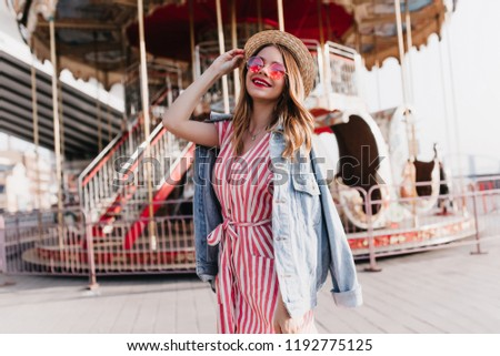 dc8a54ac400 Ecstatic girl wears denim jacket posing near carousel with sincere smile.  Outdoor photo of cute