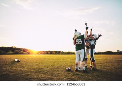 Ecstatic group of American football players standing in a huddle and raising a championship trophy in celebration