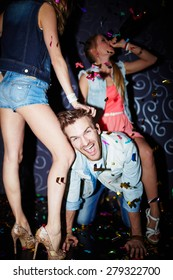 Ecstatic guy having fun with girls in night club