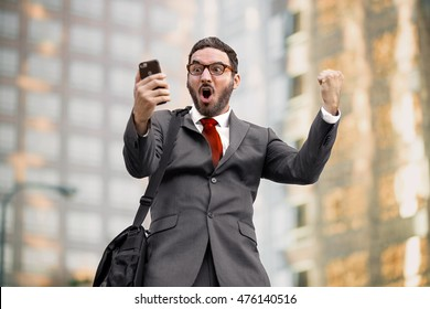 Ecstatic happy executive sales businessman cheering excited in celebration after good news