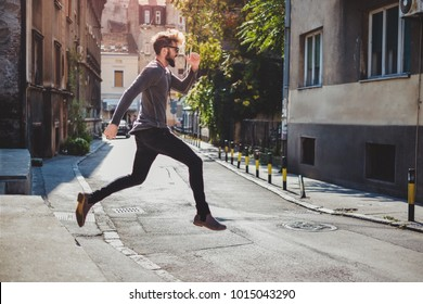 Ecstatic hipster jumps in the street with his mouth open. Runing pose in the air