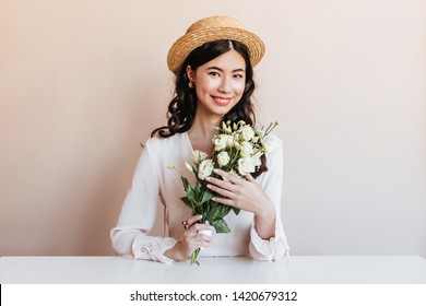 Ecstatic korean woman smiling while posing with flowers. Blithesome curly asian girl holding white eustomas.