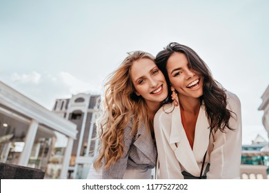 Ecstatic long-haired girls posing in spring day on sky background. Outdoor photo of two good-looking female friends.