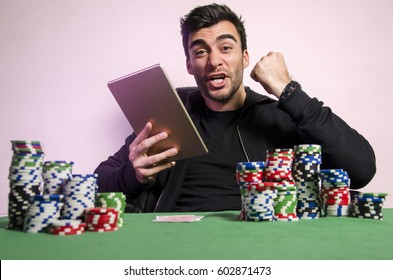 Ecstatic man with tablet playing online poker, poker win, fist in air