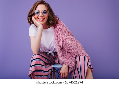 Ecstatic short-haired woman in blue glasses sitting on chair in studio. Indoor photo of pretty european lady in fluffy pink jacket posing with smile on purple background.