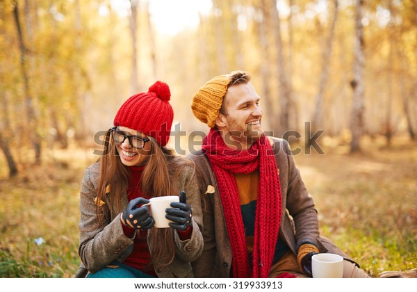 Ecstatic sweethearts with cups of tea laughing at leisure in natural environment