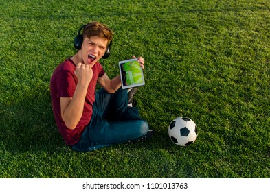 Ecstatic teen, watching soccer game on tablet while sitting on grass of soccer field