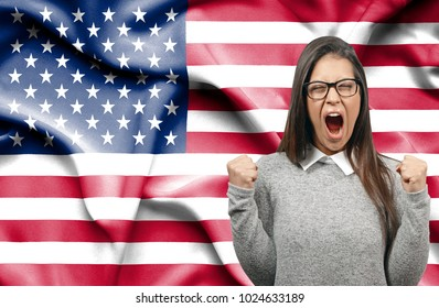 Ecstatic woman holidng fists and screaming against flag of United States of America
